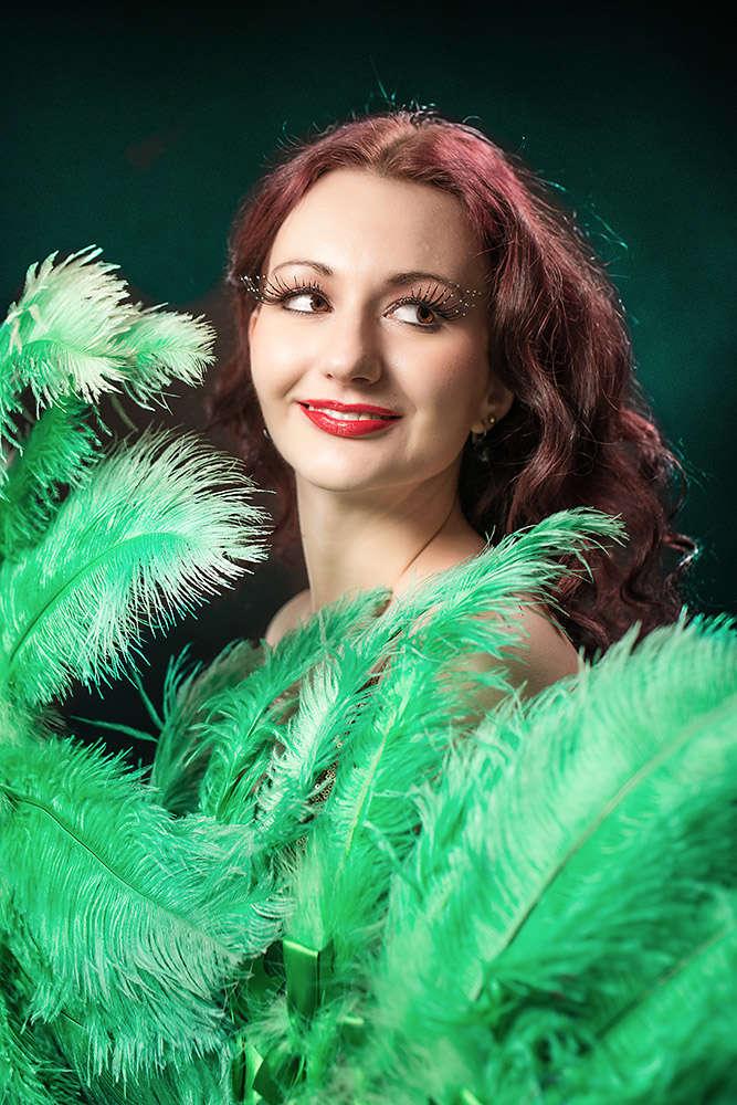 kobieta z zielonymi pawimi piórami